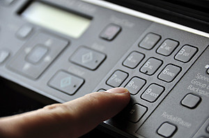 Hand pressing button on copy machine